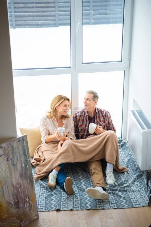 Photo for Happy couple with coffee cups sitting on floor by large window at new home - Royalty Free Image