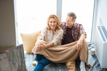 Photo pour Heureux couple assis sur le plancher de la grande fenêtre à la nouvelle maison - image libre de droit