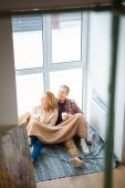 """Постер, картина, фотообои """"Счастливая пара, сидя на полу с большим окном и Холдинг чашек кофе"""""""