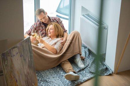 Photo pour Verres de tintements heureux couple tout en reposant sur le plancher de la grande fenêtre à la nouvelle maison - image libre de droit