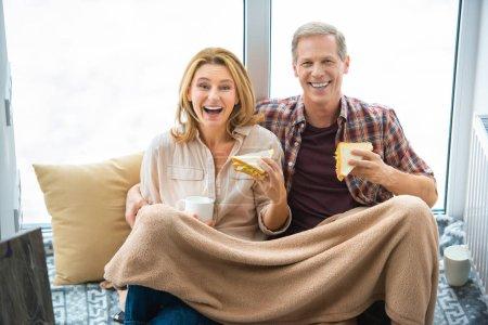 Photo pour Heureux couple mangeant des sandwiches tout en étant assis sur le plancher de la grande fenêtre - image libre de droit