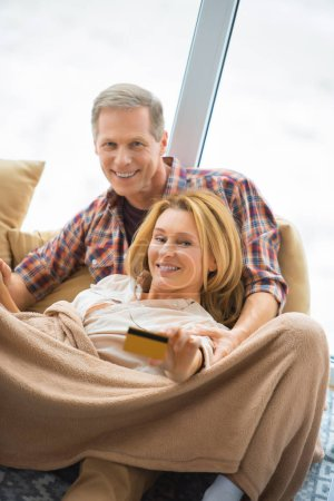 Photo for Selective focus of pretty woman showing credit card while resting with husband by large window - Royalty Free Image