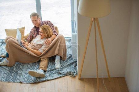 Photo pour Heureux couple utilisant l'ordinateur portable tout en reposant sur le plancher de la grande fenêtre à la nouvelle maison - image libre de droit