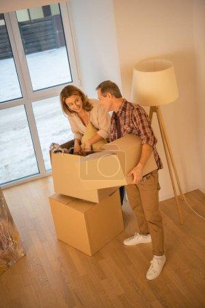 Photo pour Déballage des cartons à la maison de nouveau l'heureux couple - image libre de droit