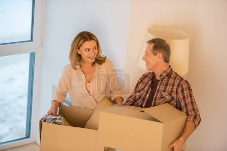 Photo for Happy couple talking while unpacking cardboard boxes at new home - Royalty Free Image
