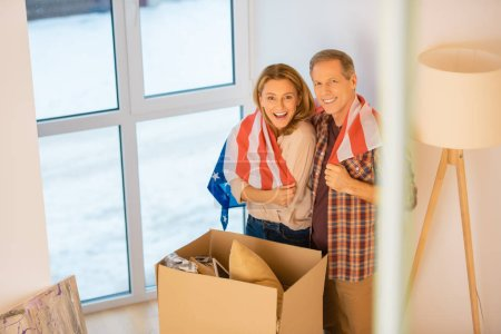 Photo for Selective focus of smiling couple standing by cardboard box and wrapping in usa national flag - Royalty Free Image