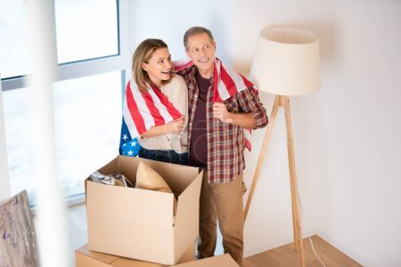 selective focus of happy couple wrapping in usa national flag while standing near cardboard boxes at new home