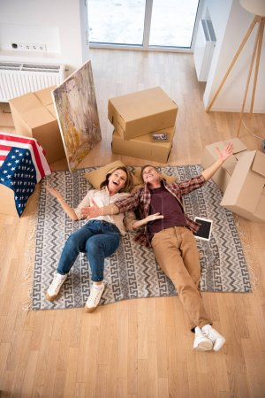 Photo for Overhead view of happy excited couple laying on floor at new home - Royalty Free Image