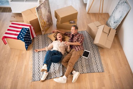 Photo for Overhead view of happy couple laying on floor surrounded by cardboard boxes - Royalty Free Image