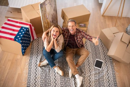 Photo for Happy excited couple sitting on fleece blanket on floor at new home and looking at camera - Royalty Free Image