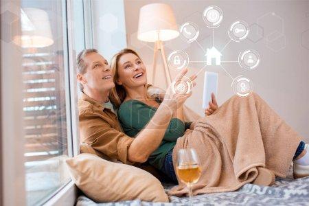 Photo pour Sourire de femme tenant la tablette numérique tout en étant assis sur le plancher avec mari, smart home concept - image libre de droit