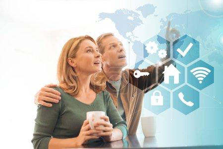 Foto de Enfoque selectivo de pareja divertida con tazas de café, concepto de casa inteligente - Imagen libre de derechos