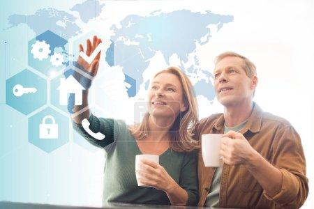 Photo pour Amusé couple tenant des tasses à café, concept maison intelligente - image libre de droit