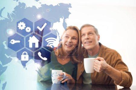 Foto de Enfoque selectivo de divertido feliz pareja sosteniendo las tazas de café, concepto de casa inteligente - Imagen libre de derechos