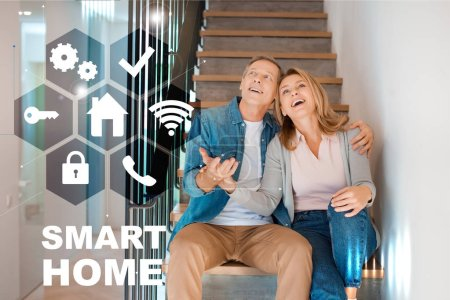Photo pour Heureux époux et épouse assis dans les escaliers au nouveau domicile, smart home concept - image libre de droit