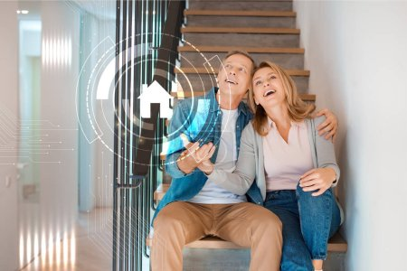 Photo for Excited couple sitting on stairs at new home, smart home concept - Royalty Free Image