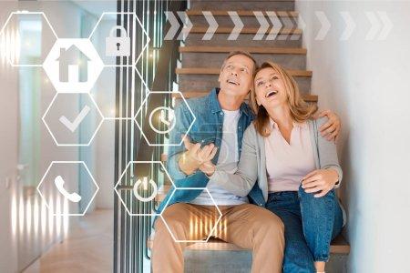 Photo pour Inspiré le couple souriant, assis sur les escaliers au nouveau concept de maison maison, smart - image libre de droit