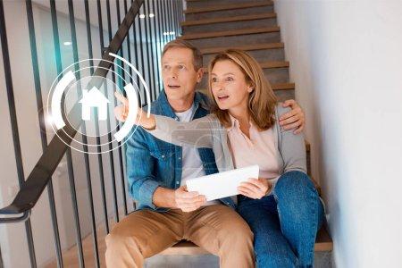 Photo pour Femme inspirée, pointant la main tout en siégeant avec mari dans les escaliers et à l'aide de tablette numérique, la notion de maison intelligente - image libre de droit