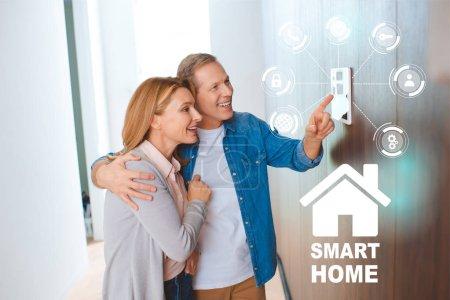 Foto de Feliz esposo abrazando al señalar en el panel de control de sistema de casa inteligente - Imagen libre de derechos