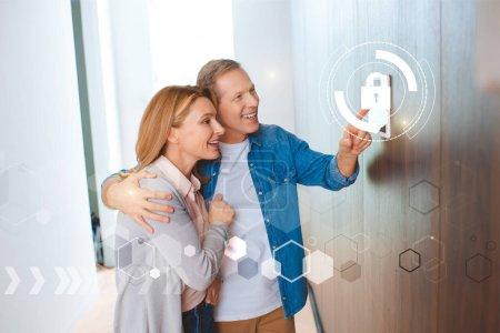Foto de Sonriente marido apuntando a panel de control de sistema de casa inteligente y abrazos feliz esposa - Imagen libre de derechos