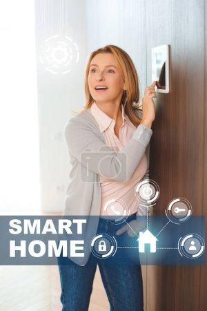 Photo pour Femme inspirée heureuse utilisant panneau de commande de maison intelligente - image libre de droit