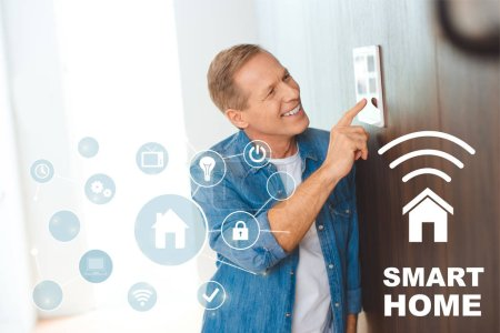 happy man using smart house control panel at new home