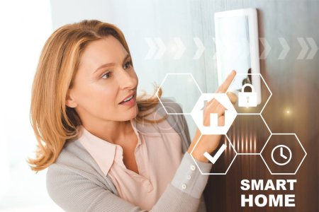 Photo for Pretty blonde woman using smart house system control panel - Royalty Free Image