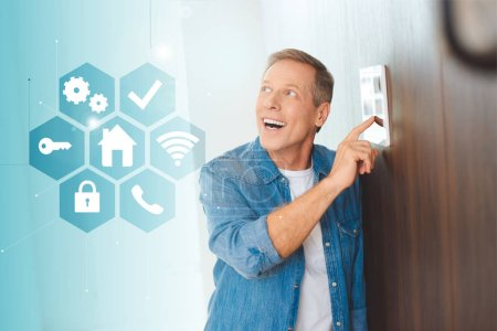 happy handsome man using smart house system control panel