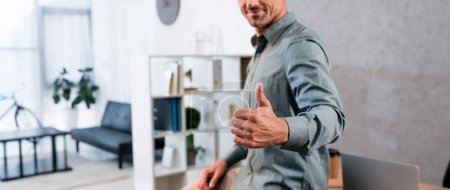 Photo for Panoramic shot of cheerful businessman showing thumb up - Royalty Free Image