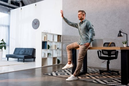 cheerful businessman waving hand and standing with hand in pocket in modern office