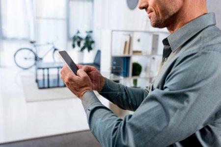 Foto de Recortada la visión del empresario con smartphone en oficina moderna - Imagen libre de derechos
