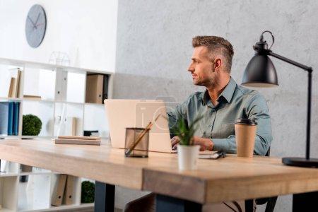 Photo pour Bel homme d'affaires, assis près de portable de bureau moderne - image libre de droit
