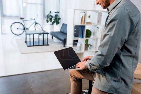 Photo pour Vue recadrée de l'homme d'affaires à l'aide d'un ordinateur portable avec écran vide dans le bureau - image libre de droit