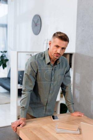 homme d'affaires sérieux debout près de l'espace de travail dans le bureau moderne