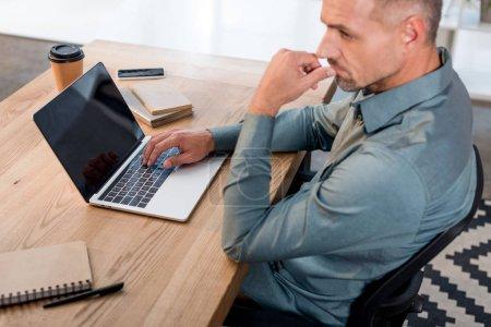 Photo pour Cher homme d'affaires utilisant un ordinateur portable avec écran blanc tout en étant assis dans un bureau moderne - image libre de droit