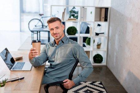 homme d'affaires joyeux tenant tasse en papier dans le bureau moderne