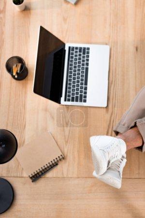 Photo pour Vue du dessus de l'ordinateur portable avec écran blanc avec les jambes masculines en baskets blanches sur la table - image libre de droit
