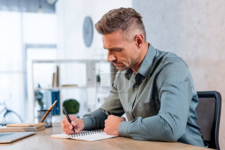 Photo for Handsome businessman writing in notebook in modern office - Royalty Free Image