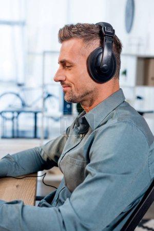 Photo pour Bel homme joyeux écoutant de la musique dans les écouteurs au bureau - image libre de droit