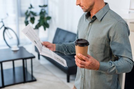 Photo for Cropped view of businessman reading newspaper and holding paper cup - Royalty Free Image