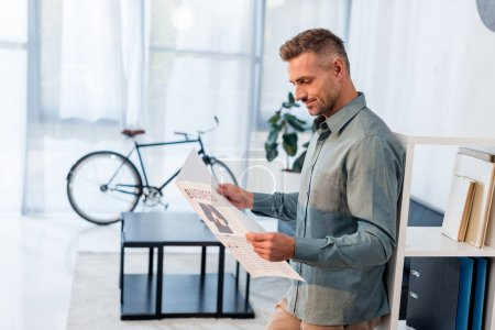 cheerful businessman reading business newspaper in modern office