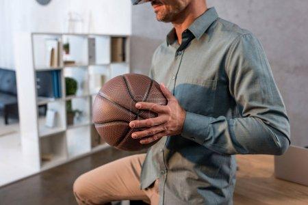 Photo pour Vue recadrée de l'homme d'affaires tenant le basket au bureau - image libre de droit