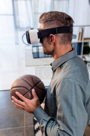 Photo pour Homme d'affaires portant casque de réalité virtuelle et tenant basket - image libre de droit