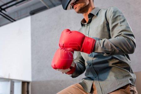 Photo pour Vue recadrée d'un homme d'affaires portant un casque de réalité virtuelle et des gants de boxe au bureau - image libre de droit