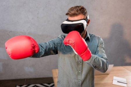 Photo pour Foyer sélectif de l'homme d'affaires portant casque de réalité virtuelle et gants de boxe au bureau - image libre de droit