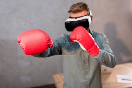 Photo for Selective focus of businessman boxing while wearing virtual reality headset in office - Royalty Free Image