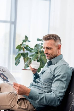Photo for Happy businessman sitting on sofa and holding cup while reading newspaper - Royalty Free Image