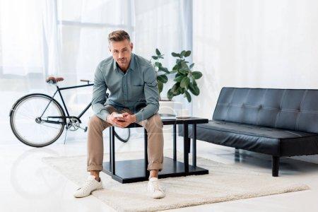Photo pour Bel homme d'affaires assis sur une table basse et utilisant un smartphone tout en regardant la caméra - image libre de droit