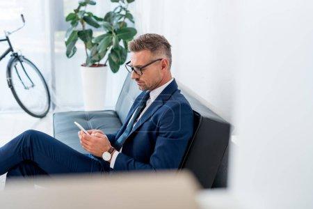 Photo pour Mise au point sélective d'un homme d'affaires sérieux utilisant un smartphone assis sur un canapé - image libre de droit