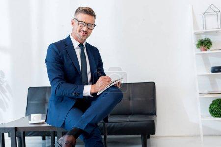 Photo pour Homme d'affaires joyeux assis sur la table basse et l'écriture dans le carnet - image libre de droit